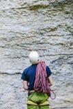 佩带在有站立在一个石岩石前面的绳索的上升的设备的年轻人 图库摄影