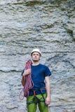 佩带在有站立在一个石岩石前面的绳索的上升的设备的年轻人 免版税库存照片
