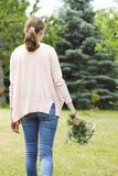 佩带在桃红色衬衣和蓝色牛仔裤的一个女孩拿着bouq 免版税库存图片
