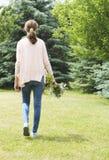 佩带在桃红色衬衣和蓝色牛仔裤的一个女孩拿着bouq 库存照片