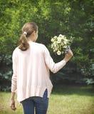 佩带在桃红色衬衣和蓝色牛仔裤的一个女孩拿着bouq 免版税库存照片