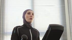 佩带在步模拟器的运动员妇女的画象一hijab在健身房 股票录像