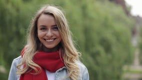佩带在红色围巾身分的年轻美女画象城市公园外 华美的妇女微笑的看 股票录像
