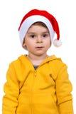 佩带在红色圣诞老人帮手帽子的小男孩 查出在空白背景 库存图片