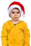 佩带在红色圣诞老人帮手帽子的小男孩 查出在空白背景 库存照片
