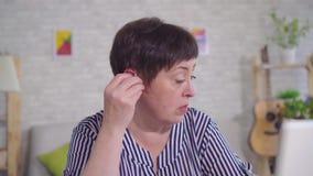 佩带在耳朵的有点聋妇女一个助听器 股票视频