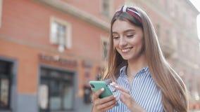 佩带在蓝色和白色镶边男式衬衫的微笑的年轻女人使用在老街道背景的智能手机身分 股票录像