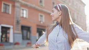 佩带在蓝色和白色镶边男式衬衫的逗人喜爱的妇女走在街道神色在转动的照相机幸福微笑 影视素材