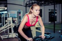 佩带在运动服的年轻运动的妇女,做在自行车的锻炼在健身房 免版税库存照片