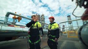 佩带在队的两名男性工作者一致的工作谈论工业安全和走在植物 影视素材