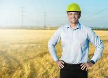 佩带在黄色盔甲的年轻蓝领工人或工程师在与宽微笑的领域站立 库存照片