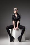 佩带在黑暗的岩石样式的积极的时尚女孩 免版税图库摄影