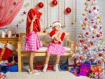 佩带在他的头的女孩圣诞老人袋子,另一个女孩是在长凳的被触犯的开会 免版税库存图片
