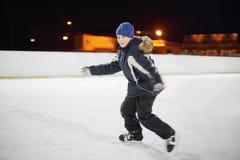 佩带在黑衣服的愉快的男孩在晚上滑冰。 免版税库存图片