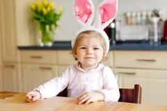 佩带复活节兔子耳朵的逗人喜爱的矮小的小孩女孩使用用色的淡色鸡蛋 打开礼物的愉快的小孩子 库存图片