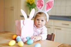 佩带复活节兔子耳朵的逗人喜爱的矮小的小孩女孩使用用色的淡色鸡蛋 打开礼物的愉快的小孩子 免版税库存图片
