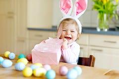 佩带复活节兔子耳朵的逗人喜爱的矮小的小孩女孩使用用色的淡色鸡蛋 打开礼物的愉快的小孩子 图库摄影