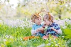 佩带复活节兔子耳朵和吃巧克力的两个孩子 免版税库存照片