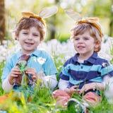 佩带复活节兔子耳朵和吃巧克力的两个小男孩 图库摄影