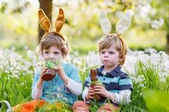 佩带复活节兔子耳朵和吃巧克力的两个小男孩 免版税图库摄影