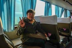 佩带外套和姿势两手指的亚裔肥胖人 图库摄影