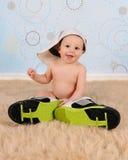 佩带大帽子和运动鞋的甜男婴 免版税库存照片