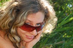 佩带妇女年轻人的表面微笑的太阳镜 免版税库存照片