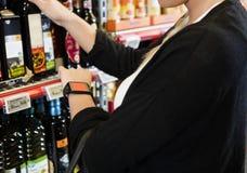佩带巧妙的手表的顾客在杂货店 免版税库存图片