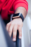 佩带巧妙的手表的黑人的手坐在汽车 免版税库存图片