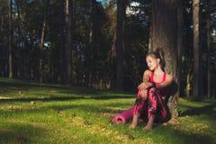 佩带巧妙的手表的年轻可爱的运动妇女为在她的锻炼以后的天享受太阳前光芒  库存图片