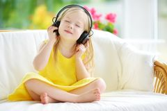 佩带巨大的无线耳机的逗人喜爱的小女孩 听到音乐的俏丽的孩子 获得的女小学生听孩子` s的乐趣 图库摄影
