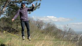 佩带帽子和胡子的一个人走slackline在风期间以高加索山脉为背景  股票视频