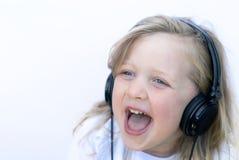 佩带年轻人的女孩耳机 图库摄影