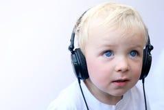 佩带年轻人的男孩愉快的耳机 库存图片