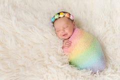 佩带彩虹的微笑的新出生的女婴色包扎 免版税库存图片