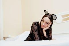 佩带性感的鞋带柳叶蒲公英属的年轻俏丽的深色的妇女,放置等待的作梦在床上 免版税库存图片
