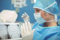 佩带手术口罩运转中剧院的女性外科医生 库存图片