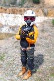 佩带摩托车成套装备、防护服装、设备、冒险旅游室外旅行、活跃旅客和红色的骑自行车的人女孩 库存照片