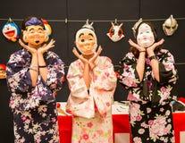 佩带日本滑稽的民间字符面具和t的亚裔游人 库存照片
