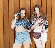 佩带时髦的明亮的成套装备、牛仔布短裤和葡萄酒照相机的两个最好的朋友女孩最佳的生活方式画象  在backgrou 库存图片