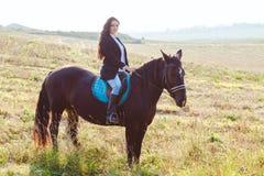 佩带时兴的骑马的华美的深色的女孩在领域的一匹马 库存照片