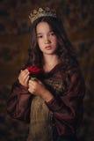佩带有一朵玫瑰的逗人喜爱的女孩画象一个冠在手上 年轻女王/王后或公主 库存图片
