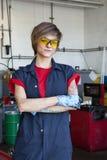 佩带有胳膊的一位愉快的技工的画象防护齿轮在汽车修理车库横渡了 免版税库存图片