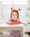佩带有铅笔的女孩圣诞老人头饰带和 库存图片
