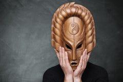 佩带木面具yin杨的人象征握他的在面具的和谐手站立在灰色背景 哲学 免版税库存照片
