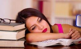 佩带桃红色上面说谎的年轻深色的妇女弯曲在有在它,疲乏的表情安置的堆的书桌书和 库存图片