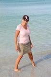 佩带桃红色丝带的海滩的可爱的妇女 免版税库存照片
