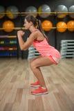 佩带桃红色体育的一名运动的妇女适合,并且教练员做着蹲在健身房 有氧和健身概念 免版税图库摄影