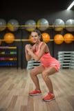 佩带桃红色体育的一名运动的妇女适合,并且教练员做着蹲在健身房 有氧和健身概念 免版税库存照片