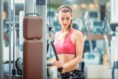 佩带桃红色健身胸罩的愉快的适合妇女,当行使在健身房时 免版税库存图片